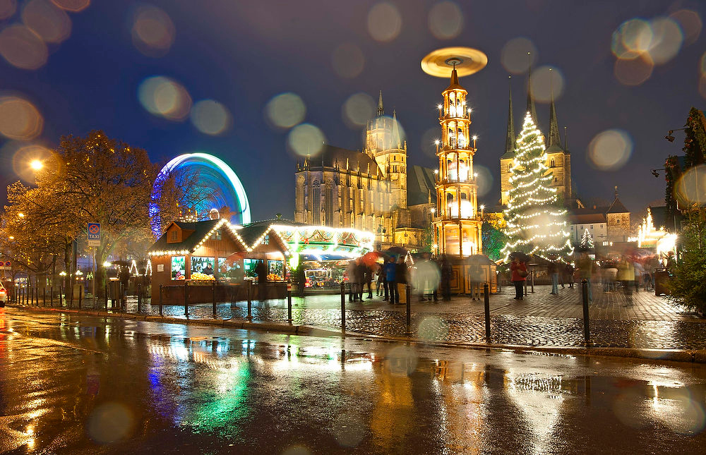 . Booths offer traditional Thuringian handcrafts and sweets and a big Ferris wheel stand at the Christmas Fair during heavy rain in front of the Mariendom (Cathedral of Mary), center left,  and St. Severi\'s Church, right,  in Erfurt, central Germany, Wednesday, Nov. 28, 2012. The Erfurt Christmas Market is one of the most beautiful Christmas Markets in Germany. The square is  decorated with a huge, candle-lit Christmas tree and a large, hand-carved nativity scene. (AP Photo/Jens Meyer)