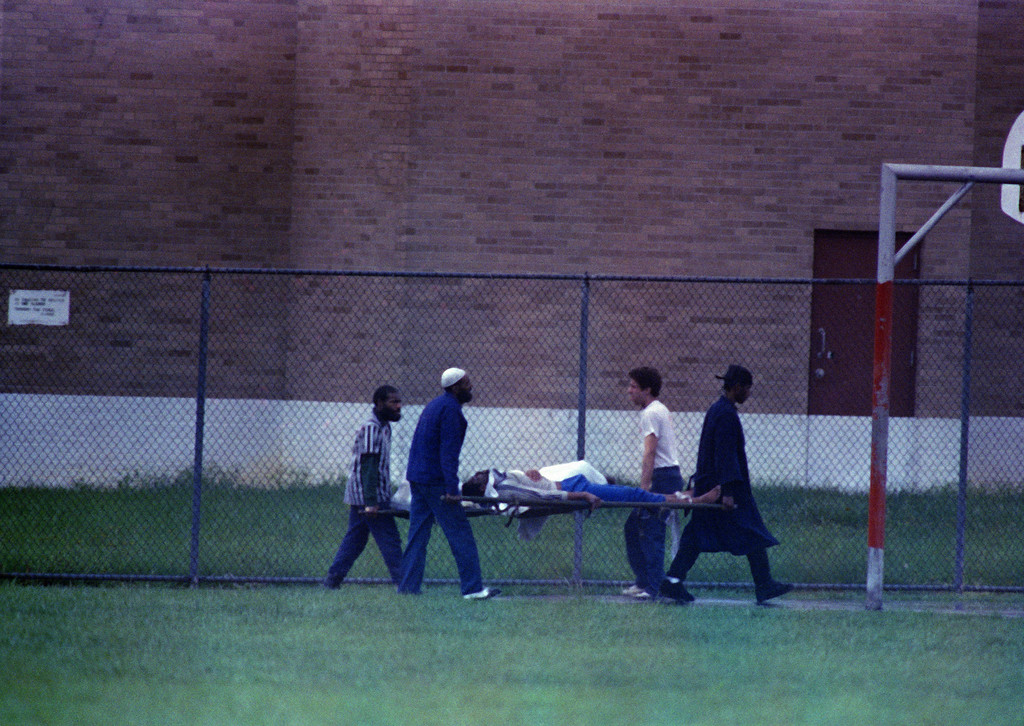 . Inmates carry inmates on stretchers from the cell block of the Southern Ohio Correctional Facility in Lucasville, Ohio, where they have been barricaded for 10 days, April 21, 1993. One prison guard and seven inmates have died in the riot. (AP Photo/Lennox McLendon/Pool)