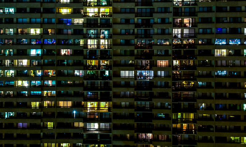 A high rise apartment complex at night mimics the glut of cable television with hundreds of channels of entertaining visions. Each window providing a separate life story.