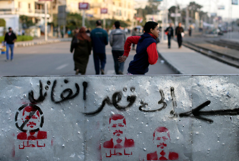 ". Egyptian protesters are seen near the presidential palace in Cairo, Egypt, Saturday, Dec. 8, 2012. Egypt\'s military has warned of \'disastrous consequences\' if the political crisis gripping the country is not resolved through dialogue. Arabic reads, ""to the killer palace.\""(AP Photo/Hassan Ammar)"
