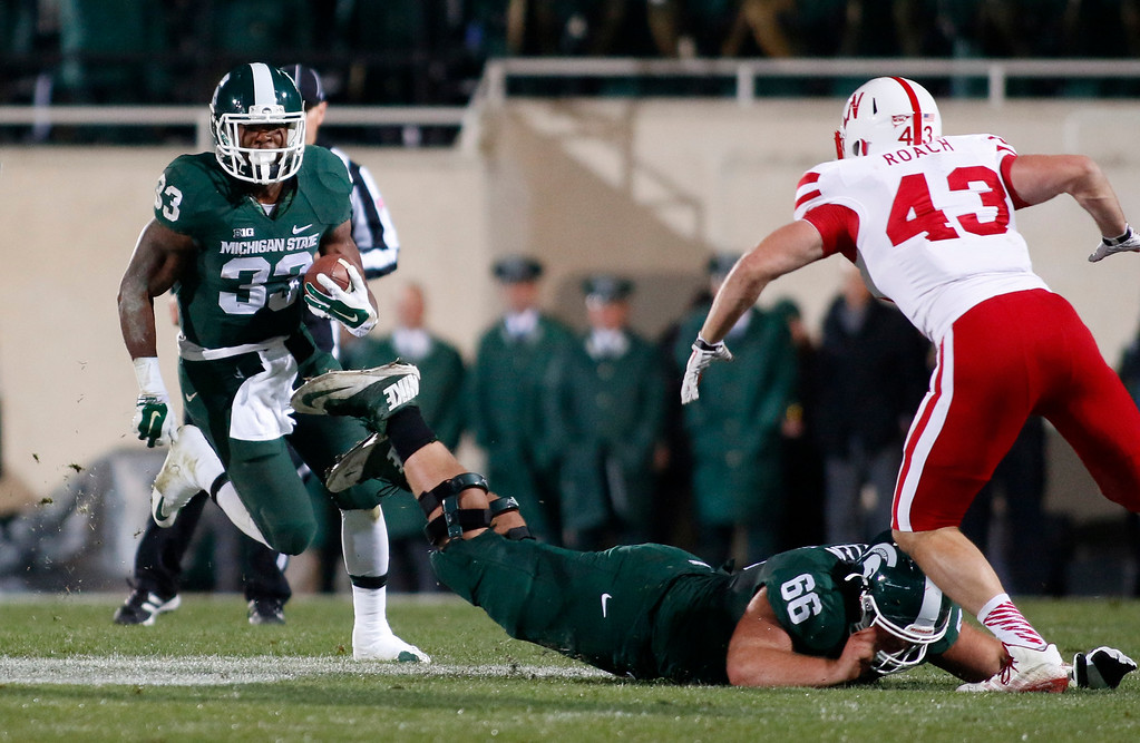 . Michigan State\'s Jeremy Langford (33) rushes against Nebraska\'s Trevor Roach (43) as Michigan State\'s Jack Allen (66) tries to block during the first quarter of an NCAA college football game, Saturday, Oct. 4, 2014, in East Lansing, Mich. (AP Photo/Al Goldis)