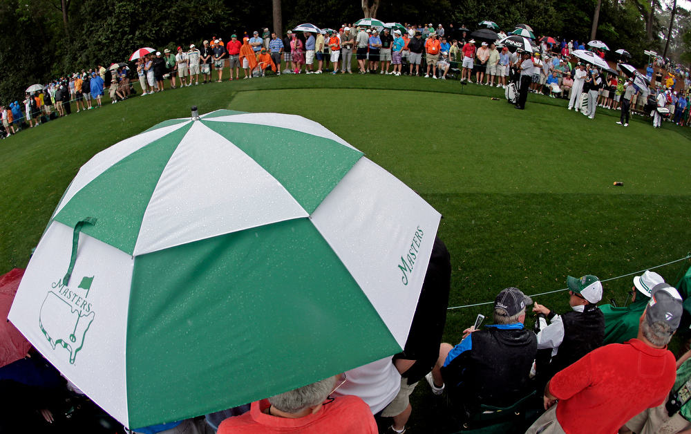 Description of . From left, Angel Cabrera, of Argentina, Sergio Garcia, of Spain, and Adam Scott, of Australia, wait to tee off in the rain on the fourth hole during the second round of the Masters golf tournament Friday, April 12, 2013, in Augusta, Ga. (AP Photo/Charlie Riedel)