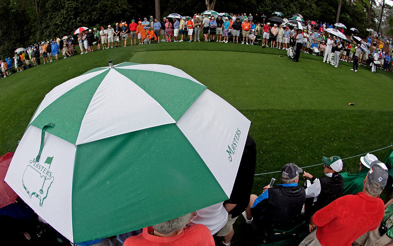 . From left, Angel Cabrera, of Argentina, Sergio Garcia, of Spain, and Adam Scott, of Australia, wait to tee off in the rain on the fourth hole during the second round of the Masters golf tournament Friday, April 12, 2013, in Augusta, Ga. (AP Photo/Charlie Riedel)
