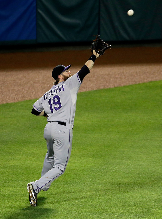 . Colorado Rockies left fielder Charlie Blackmon (19) reaches up to grab a fly out by Texas Rangers\' Adrian Beltre in the seventh inning of a baseball game, Thursday, May 8, 2014, in Arlington, Texas.  The Rangers won 5-0. (AP Photo/Tony Gutierrez)