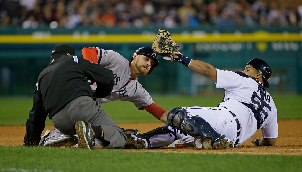 . Detroit Tigers\' Brayan Pena takes the throw as Boston Red Sox\'s Will Middlebrooks slides safely to third in the ninth inning during Game 5 of the American League baseball championship series Thursday, Oct. 17, 2013, in Detroit. At left is umpire Rob Drake.  (AP Photo/Matt Slocum)