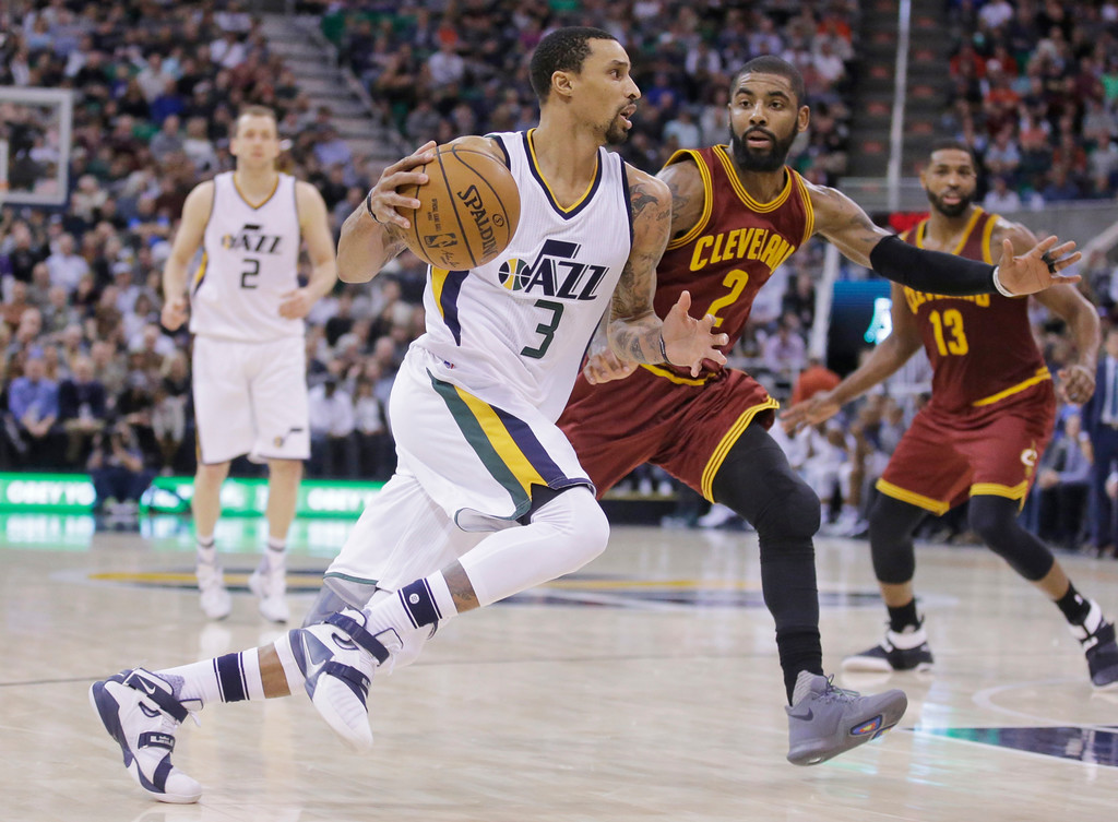 . Utah Jazz guard George Hill (3) drives around Cleveland Cavaliers guard Kyrie Irving (2) during the second half of an NBA basketball game Tuesday, Jan. 10, 2017, in Salt Lake City. The Jazz won 100-92. (AP Photo/Rick Bowmer)