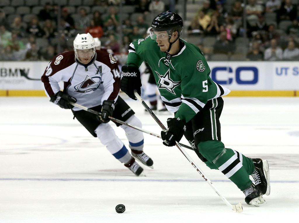 . Dallas Stars defenseman Jamie Oleksiak (5) moves the puck as Colorado Avalanche left wing Alex Tanguay (40) pressures in the second period of a preseason NHL hockey game on Thursday, Sept. 26, 2013, in Dallas. (AP Photo/Tony Gutierrez)