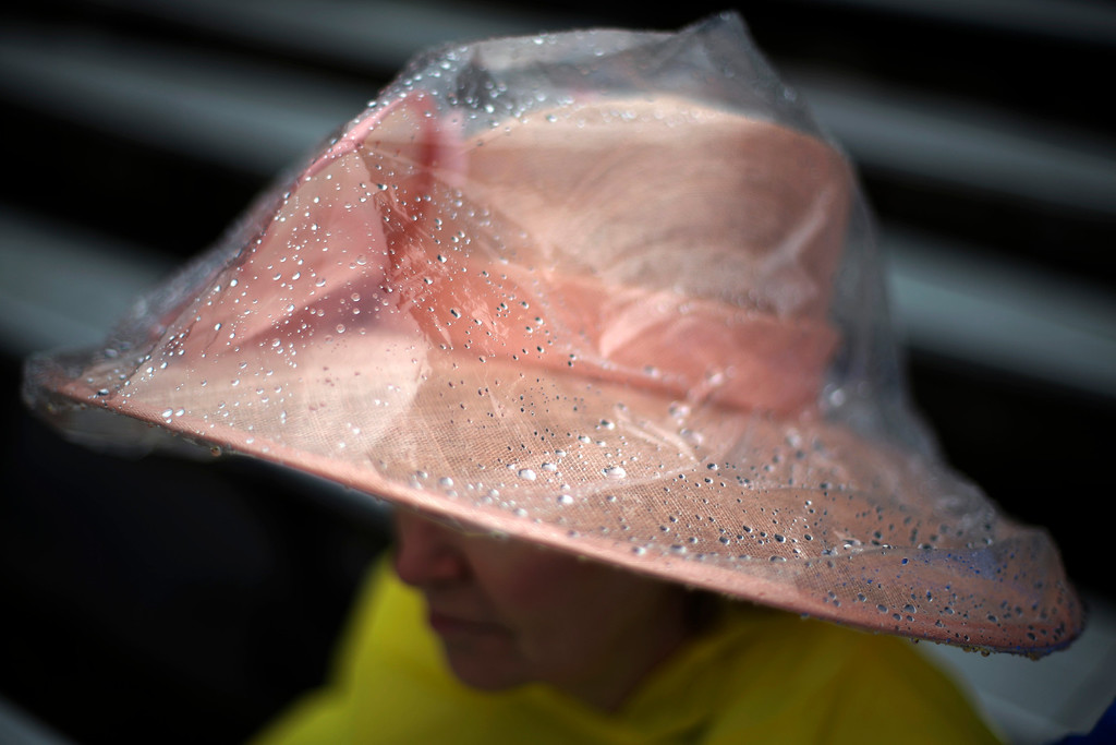 . Brenda Williams, from Tulsa, Okla, waits in the rain for the 139th Kentucky Derby at Churchill Downs Saturday, May 4, 2013, in Louisville, Ky. (AP Photo/David Goldman)