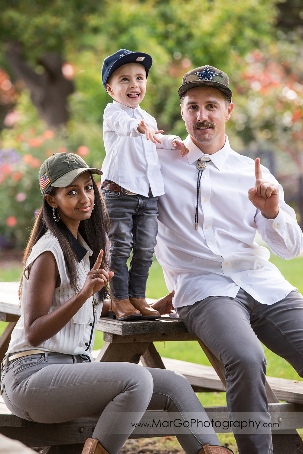 portrait of family of 3 in white shirt and gray jeans sitting on the bench in Shinn Historical Park and Arboretum in Fremont
