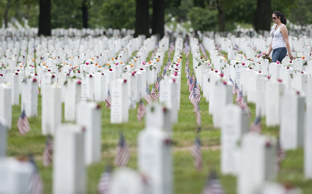 . A woman carries flowers past grave markers in Section 60, the area of the cemetery primarily for members of the military killed in the wars in Iraq and Afghanistan, during Memorial Day at Arlington National Cemetery in Arlington, Virginia, May 27, 2013.  SAUL LOEB/AFP/Getty Images