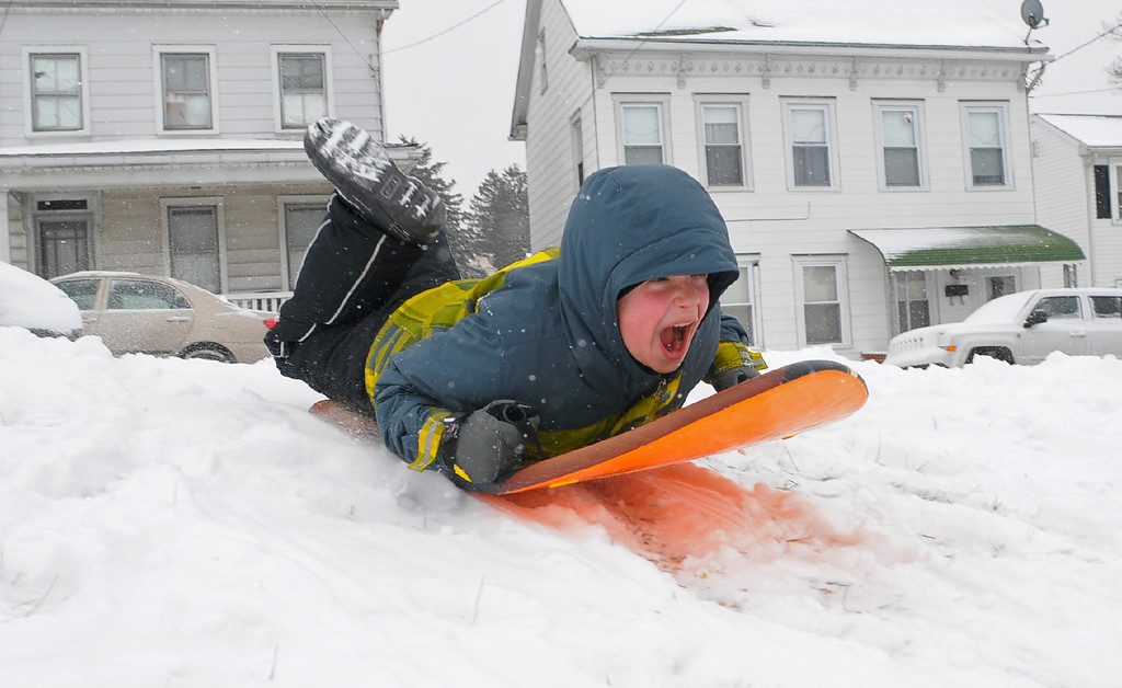 . Reese Felty, 9, Schuylkill Haven, rides his sled down a hill at the Schuylkill Haven, Pa., high school Tuesday, Jan. 21, 2014. The National Weather Service has issued a winter storm warning for Tuesday\'s storm with public schools closed in parts of central Pennsylvania and elsewhere while Philadelphia public schools are dismissing classes early.    (AP Photo/ The Republican-Herald, Andy Matsko)