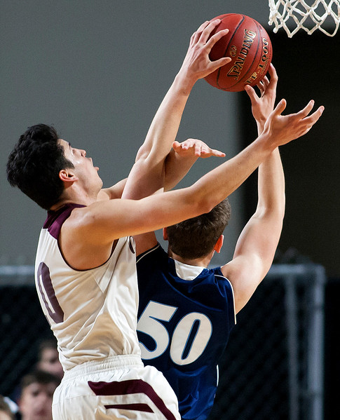 BANGOR, Maine -- 02/18/2017 -- Orono's Nate Desisto (left) fouls Presque Isle's Patrick  T. Cash during their Class B boys basketball quarterfinal game at the Cross Insurance Center in Bangor Saturday. Ashley L. Conti | BDN