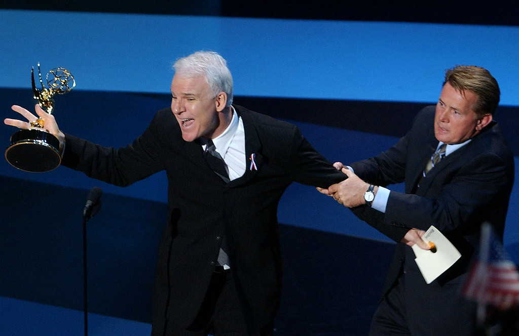 . US actor Steve Martin (L) grabs an Emmy Award from presenter Martin Sheen (R) as a joke about winners not turning up at the 53rd Emmy Awards at the Shubert Theatre, in Los Angeles, 04 November 2001.  A subdued version of the Emmy awards for excellence in US television took time out to thank the international community for its solidarity in the wake of the September 11 terror attacks on the United States.   LUCY NICHOLSON/AFP/Getty Images