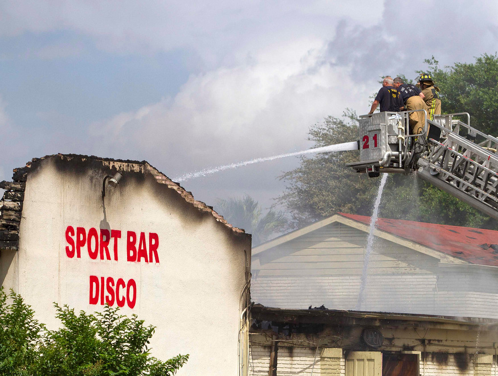 . Firefighters spray water on a five-alarm fire at the Southwest Inn restaurant and hotel where at least six firefighters were injured, two of them critically, in southwest Houston May 31, 2013.     REUTERS/Richard Carson