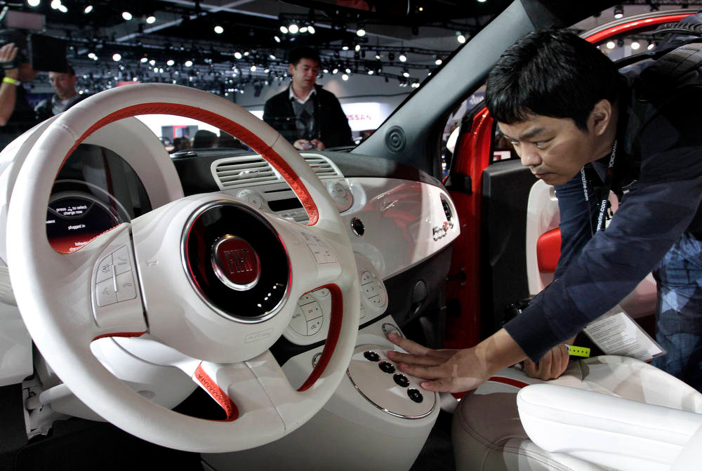 . An attendee views the interior of a Fiat SpA 500e vehicle during the LA Auto Show in Los Angeles, California, U.S., on Wednesday, Nov. 28, 2012. After returning to the U.S. with its 500 subcompact in 2010, Fiat plans to introduce an electric version at the Los Angeles Auto Show today. Photographer: Jonathan Alcorn/Bloomberg