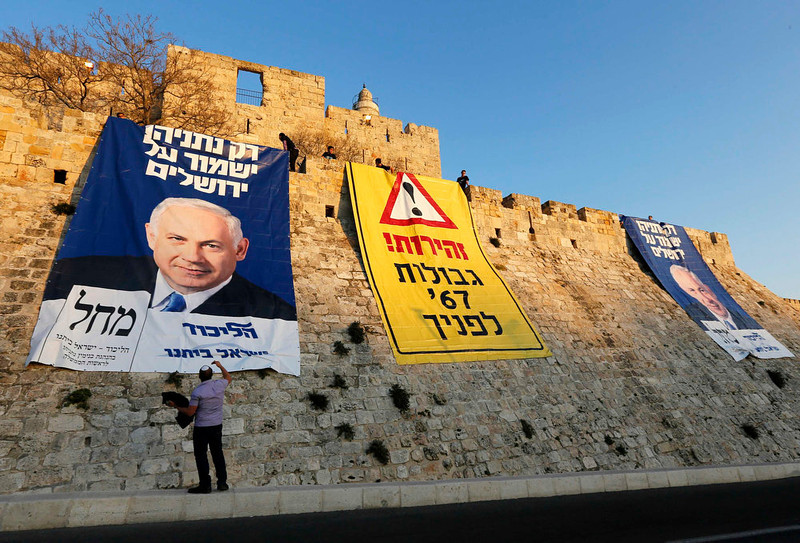 """. A man stands next to campaign banners depicting Israel\'s Prime Minister Benjamin Netanyahu after Likud-Yisrael Beitenu activists draped them on walls surrounding Jerusalem\'s Old City January 20, 2013. Netanyahu said on Saturday a country with as many enemies as Israel cannot afford a weak ruling party, after polls ahead of Tuesday\'s parliamentary election showed a slide in his support. The banners read (L and C) \""""Only Netanyahu will protect Jerusalem\"""" and \""""Warning! \'67 borders ahead\"""". REUTERS/Ronen Zvulun"""