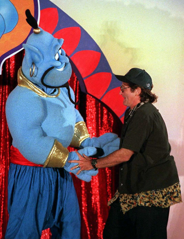 ". Actor-comedian Robin Williams dances 10 July in Los Angeles with the Disney character ""Genie\"" during a celebration for the scheduled 13 August world release of the film \""Aladdin and the King of Thieves\"".  Williams who  plays the voice of \""Genie\"" in the third sequel to the Aladdin trilogy entertained an audience of 5,000.  The movie will be the first in the trilogy to be released direct to the home video market instead of in the movie theaters.  JOHN T. BARR/AFP/Getty Images"