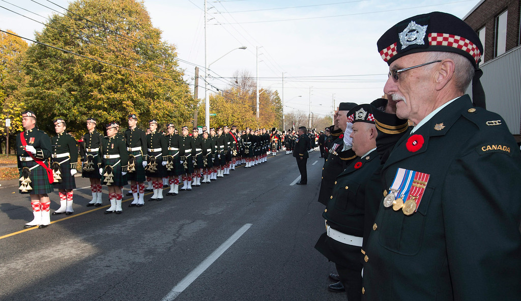 . Highlander veterans, right, salute during the funeral procession for Cpl. Nathan Cirillo in Hamilton, Ontario,  on Tuesday, Oct. 28, 2014. (AP Photo/The Canadian Press, Frank Gunn)