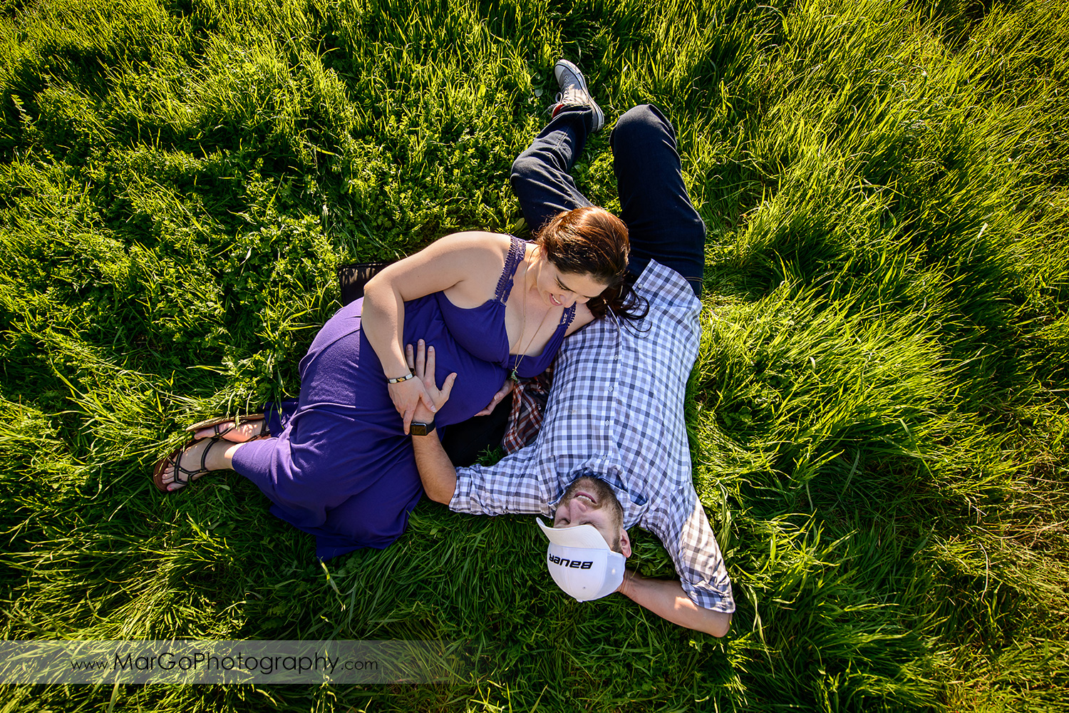 man in checkered shirt and pregnant woman in long violet dress on the green grass during maternity session at Ulistac Natural Area in Santa Clara