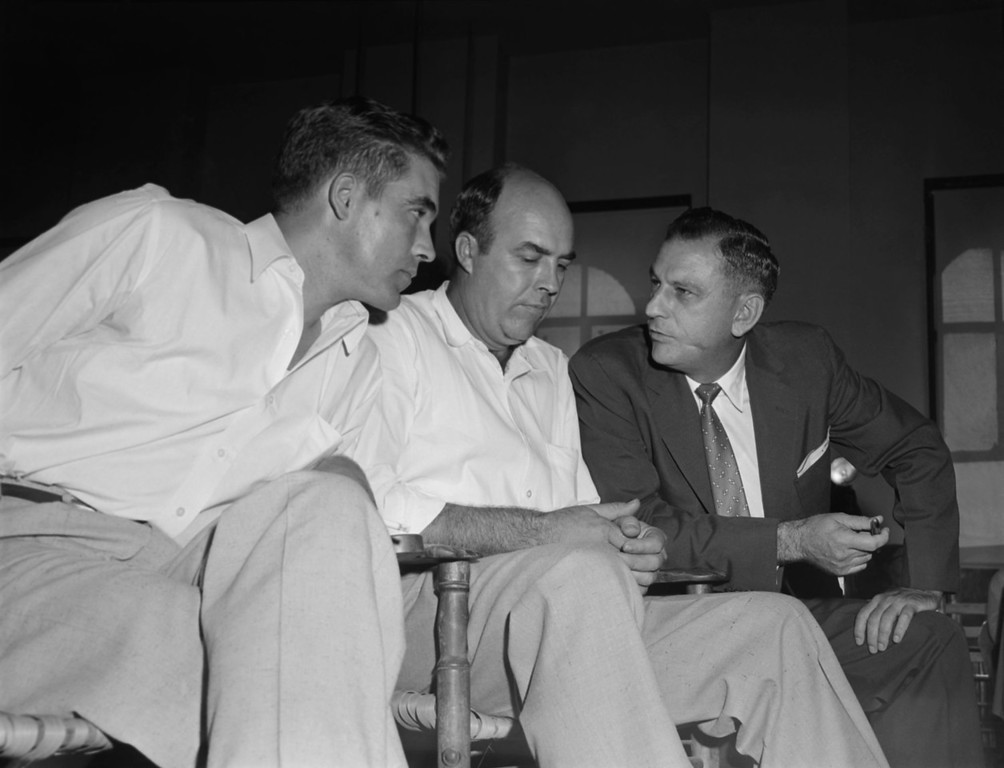 ". Half-brothers Roy Bryant, left, and J.W. Milam, center, listen to their attorney, J.W. Kellum, as they sit in the courtroom, Sept. 23, 1955, in Sumner, Miss.,  prior to the opening of their first degree murder trial in Sumner.  The half-brothers are accused in the brutal murder of 14-year-old Chicago native, Emmett Till, who is black, for ""wolf-whistling\"" at Bryant\'s wife. (AP Photo)"