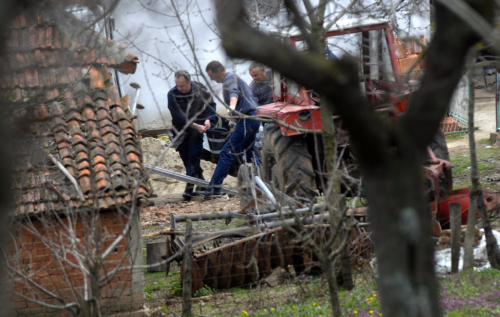 . Serbian police officers carry a body of a shooting victim in the village of Velika Ivanca, 40 kilometers south of capital Belgrade, on April 9, 2013. A man shot dead 13 relatives and neighbors, including a two-year-old child, in a tiny Serbian village on Tuesday, in the country\'s worst killing spree in two decades.  AFP PHOTO / ALEXA STANKOVIC