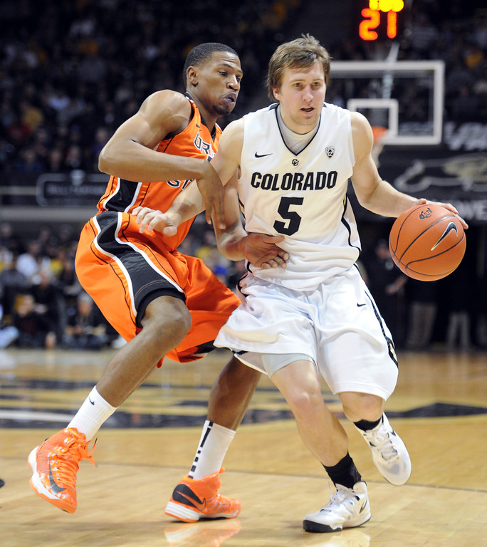 . Eli Stalzer drives on Ahmad Starks of OSU during the first half of the March 9, 2013 game in Boulder.    (Cliff Grassmick/Boulder Daily Camera)