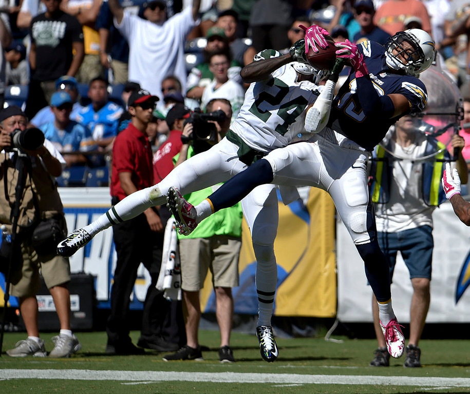 . New York Jets defensive back Phillip Adams intercepts a pass intended for San Diego Chargers wide receiver Keenan Allen during the first half of an NFL football game, Sunday, Oct. 5, 2014, in San Diego. (AP Photo/Denis Poroy)