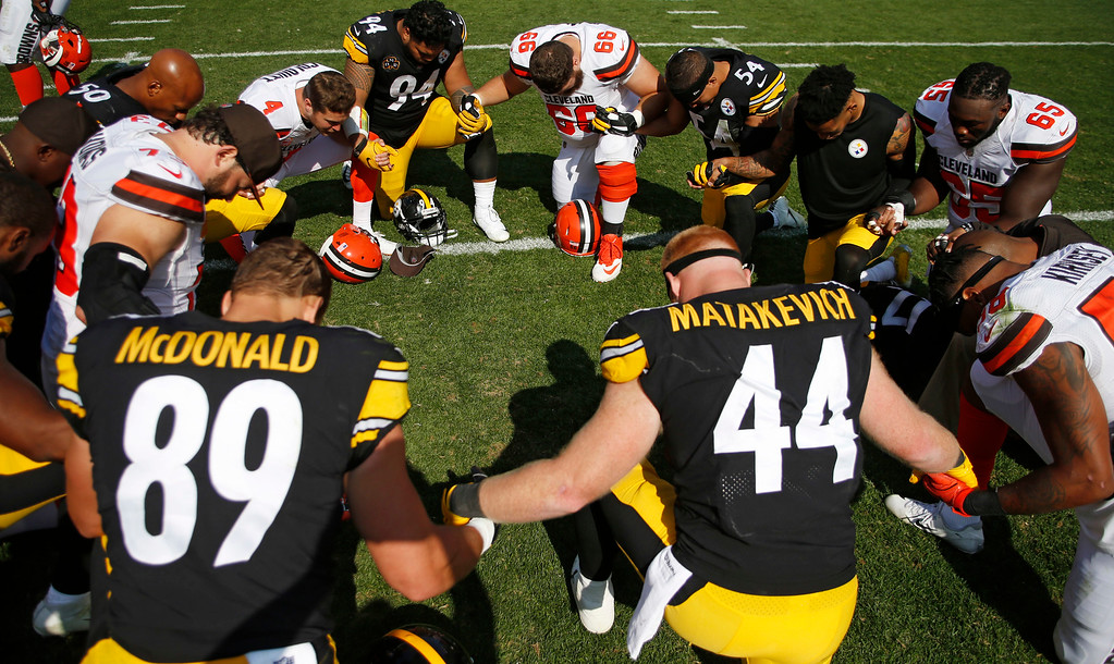 . Members of the Cleveland Browns and the Pittsburgh Steelers kneel to pray after an NFL football game, Sunday, Sept. 10, 2017, in Cleveland. (AP Photo/Ron Schwane)