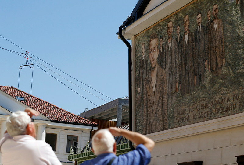 ". People look at a mosaic depicting Gavrilo Princip, the Bosnian-Serb nationalist who assassinated Archduke Franz Ferdinand in 1914, and other members of ""Mlada Bosna\"" movement in the Bosnian town of Visegrad,140 kilometers east of Sarajevo, Saturday, June 28, 2014. Marking the centennial of the beginning of World War I in their own way, Bosnian Serbs in Visegrad on Saturday unveiled a mosaic of the man who ignited the war by assassinating the Austro-Hungarian crown prince on June 28, 1914. (AP Photo/Darko Vojinovic)"