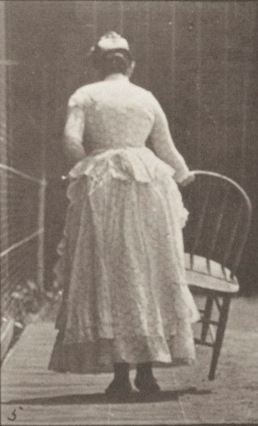 Woman in long dress with parasol in left hand placing a chair and sitting