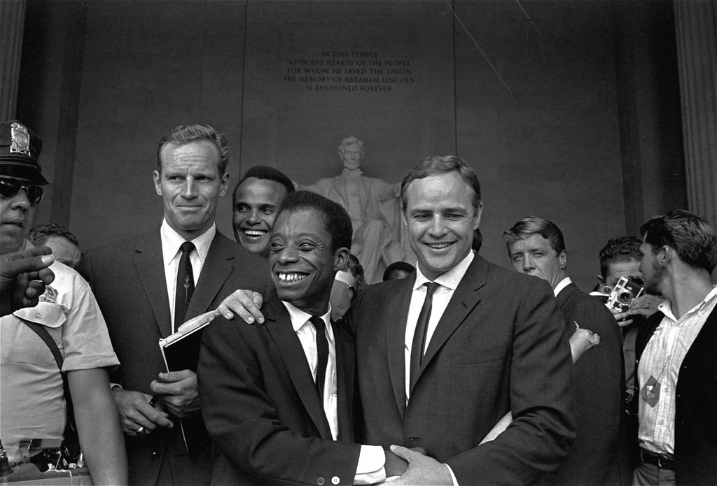. Actor Marlon Brando, right, poses with his arm around James Baldwin, author and civil rights leader, in front of the Lincoln statue at the Lincoln Memorial, August 28, 1963, during the March on Washington demonstration ceremonies which followed the mass parade.  Posing with them are actors Charlton Heston, left, and Harry Belafonte. (AP Photo, FILE)