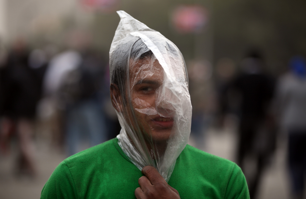 Description of . An Egyptian protester covers his face with a plastic bag during clashes with riot police, not seen, near Tahrir Square, Cairo, Egypt, Monday, Jan. 28, 2013. Health and security officials say a protester has been killed in clashes between rock-throwing demonstrators and police near Tahrir Square in central Cairo. The officials say the protester died Monday on the way to the hospital after being shot. (AP Photo/Khalil Hamra)