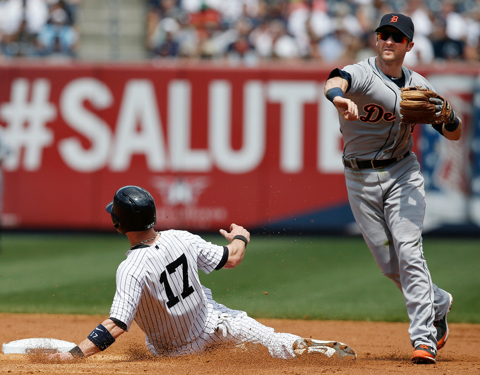 . Detroit Tigers shortstop Andrew Romine (27) forces out New York Yankees Brendan Ryan after Brett Gardner grounded into a third-inning double play in a baseball game at Yankee Stadium in New York, Thursday, Aug. 7, 2014.  (AP Photo/Kathy Willens)