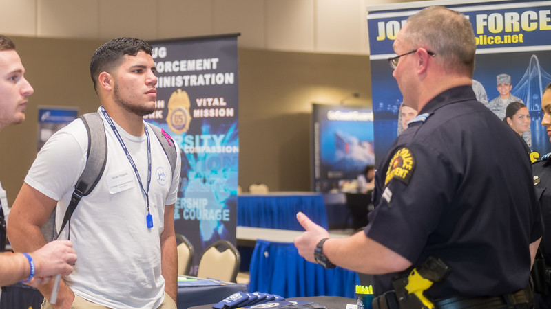 Israel Acevedo talks to a recruiter from the Dallas Police Department during the Government, Veterans, and Criminal Justice Career Fair.