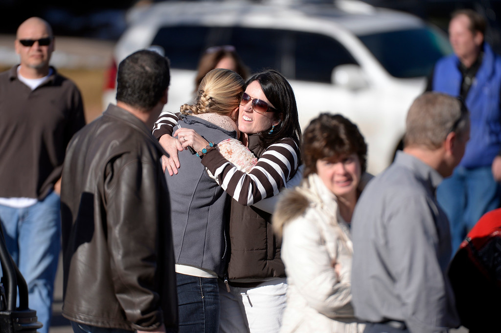 . CENTENNIAL, CO - Arapahoe High School students parents hug each other as they wait to hear world from their son or daughter as they stand on the street near the tennis courts. The students were taken to the football field for safety. A gunman was spotted inside Arapahoe High School December 13, 2013. The gunman was targeting a teacher at the school. The gunman shot two students in the process and then turned the gun on himself. DECEMBER 13:  (John Leyba, The Denver Post)