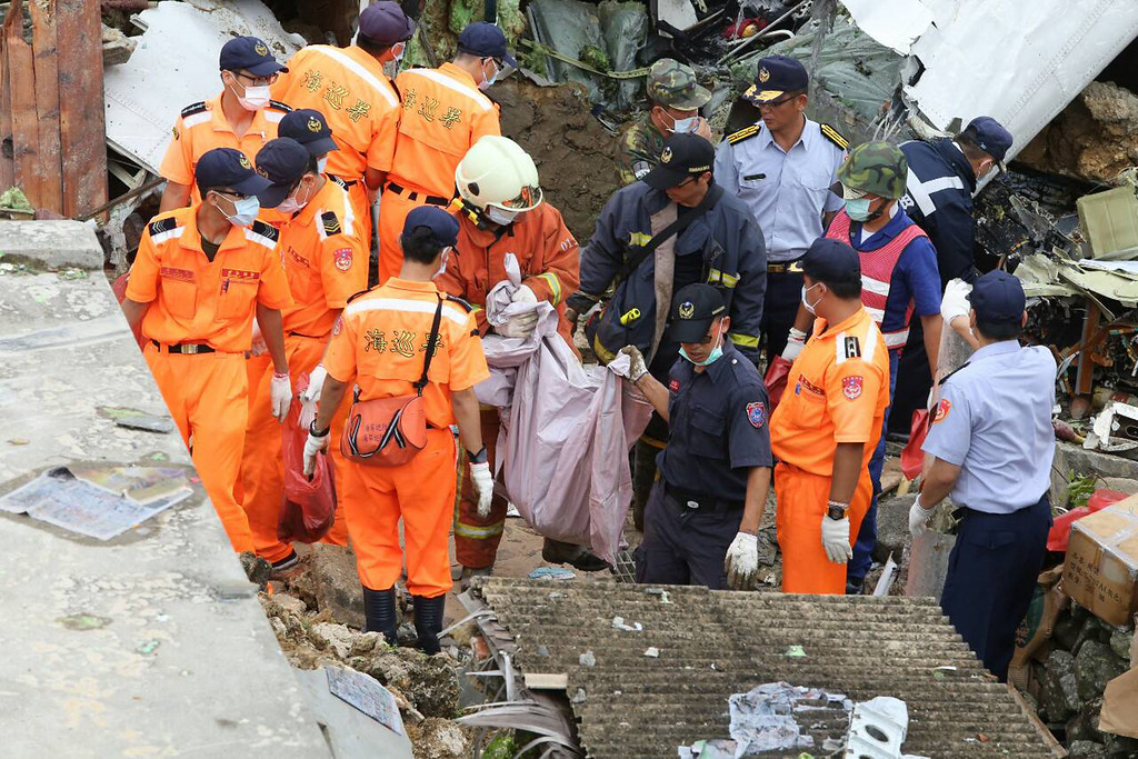 . Rescue workers survey the wreckage of TransAsia Airways Flight GE222 which crashed on the Taiwanese island of Penghu Thursday, July 24, 2014.  (AP Photo) TAIWAN OUT