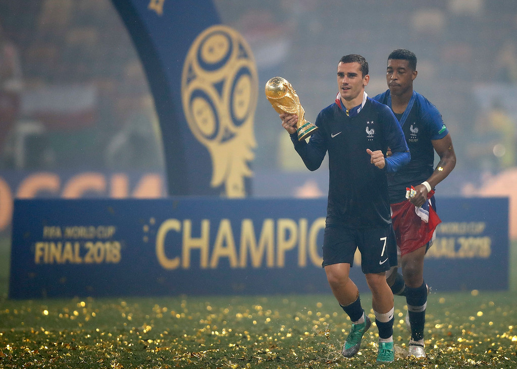 . France\'s Antoine Griezmann holds the World Cup trophy as he jogs around the pitch after France defeated Croatia in the final match between France and Croatia at the 2018 soccer World Cup in the Luzhniki Stadium in Moscow, Russia, Sunday, July 15, 2018. France won the game 4-2. (AP Photo/Francisco Seco)