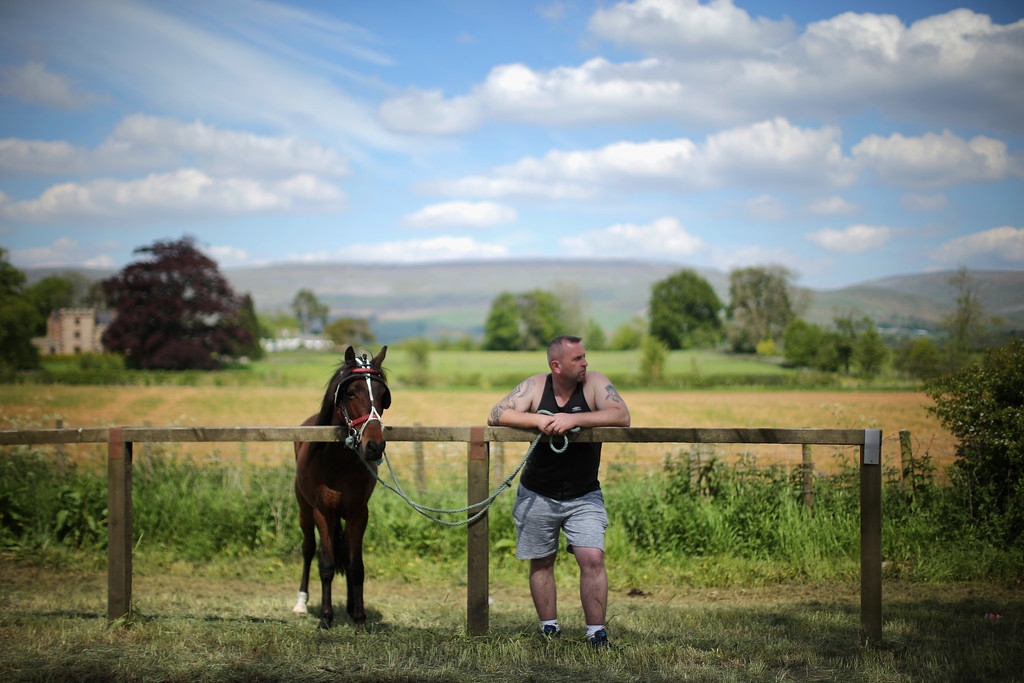 . A traveller man watches horses being raced along the \'Mad Mile\' during the Appleby Horse Fair on June 4, 2015 in Appleby, England. The Appleby Horse Fair has existed under the protection of a charter granted by James II since 1685 and is one of the key gathering points for the Romany, gypsy and traveling community. The fair is attended by about 5,000 travelers who come to buy and sell horses. The animals are washed and groomed before being ridden at high speed along the \'mad mile\' for the viewing of potential buyers.  (Photo by Christopher Furlong/Getty Images)