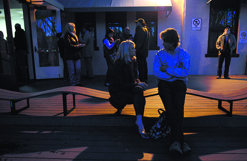 . Santa Cruz residents who came to the Louden Nelson Community Center Wednesday night to pay their respects to the two  officers slain in Tuesday\'s shooting visit with each other on the front porch of the Community Center (Matthew Hintz/Sentinel).