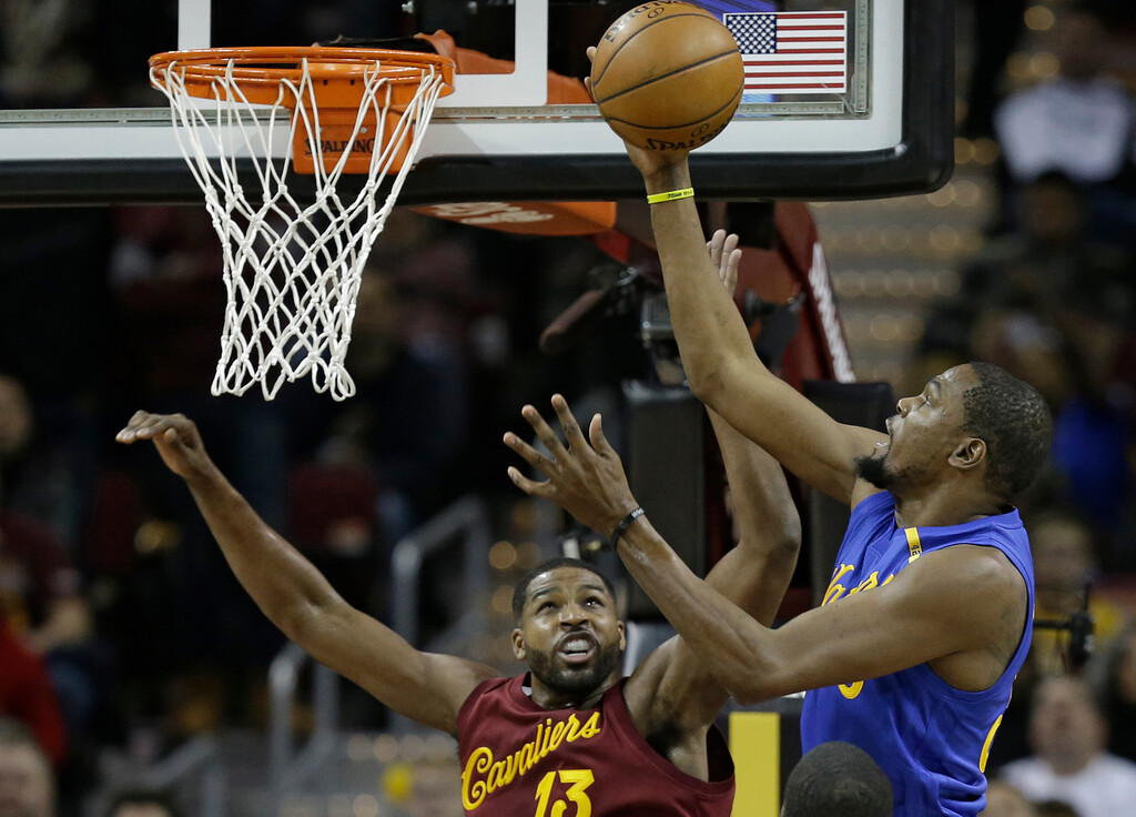 . Golden State Warriors\' Kevin Durant, right, drives to the basket against Cleveland Cavaliers\' Tristan Thompson in the first half of an NBA basketball game, Sunday, Dec. 25, 2016, in Cleveland. (AP Photo/Tony Dejak)