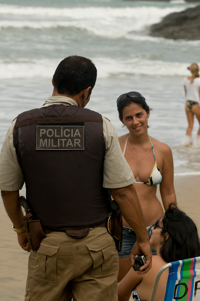 A police officer chats with two young ladies on the beach in Itacare, Bahia, Brazil.