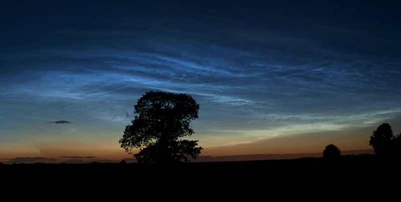 Midnight darkness turns to day from the glow of noctilucent clouds captured above the Leics skyline on June 17/18th 2009.   This remarkable photograph was taken at midnight and shows the rare phenomenon of 'night shining.' The shimmering clouds form at an altitude of around 55 miles above sea level and are made up of tiny ice droplets. Because they are so high up in the atmosphere the sun is able to illuminate the clouds from below the horizon.  Called 'noctilucent' clouds, which literally means 'night-shining' in Latin, they are normally spotted in polar regions during the summer months.  Noctilucent cloud formations are the highest on Earth where temperatures can plunge below -130C (-200F) and winds peak at 300mph. They appear in the mesosphere, which is between 30miles and 50miles above the Earth's surface.   Clouds are made up of ice crystals and scientists are baffled as to how these form in an arid layer that is several million times drier than the Sahara Desert. But their prevalence in the summer months might be one clue. Upwelling winds in the summertime carry water vapor from the moist lower atmosphere toward the mesosphere.  Apparently the water droplets also need dust particles to stick to to create the ice crystals. This could explain why the phenomenon was first recorded in 1885, two years after the Krakatoa eruption, when several tonnes of carbon dioxide, ash and dust were emitted into the atmosphere. However scientists do not know why the clouds have become more common since then rather than fading away. They have speculated that debris from space may be the answer.  Taken with Olympus E3, 12-60mm SWD.