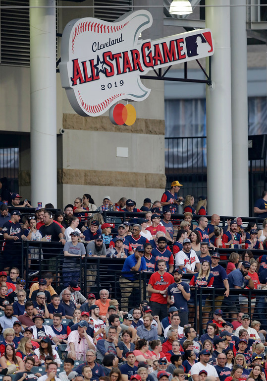 . The 2019 All-Star Game logo rests above Cleveland Indians fans watching a baseball game between the Minnesota Twins and the Indians, Wednesday, Aug. 8, 2018, in Cleveland. (AP Photo/Tony Dejak)