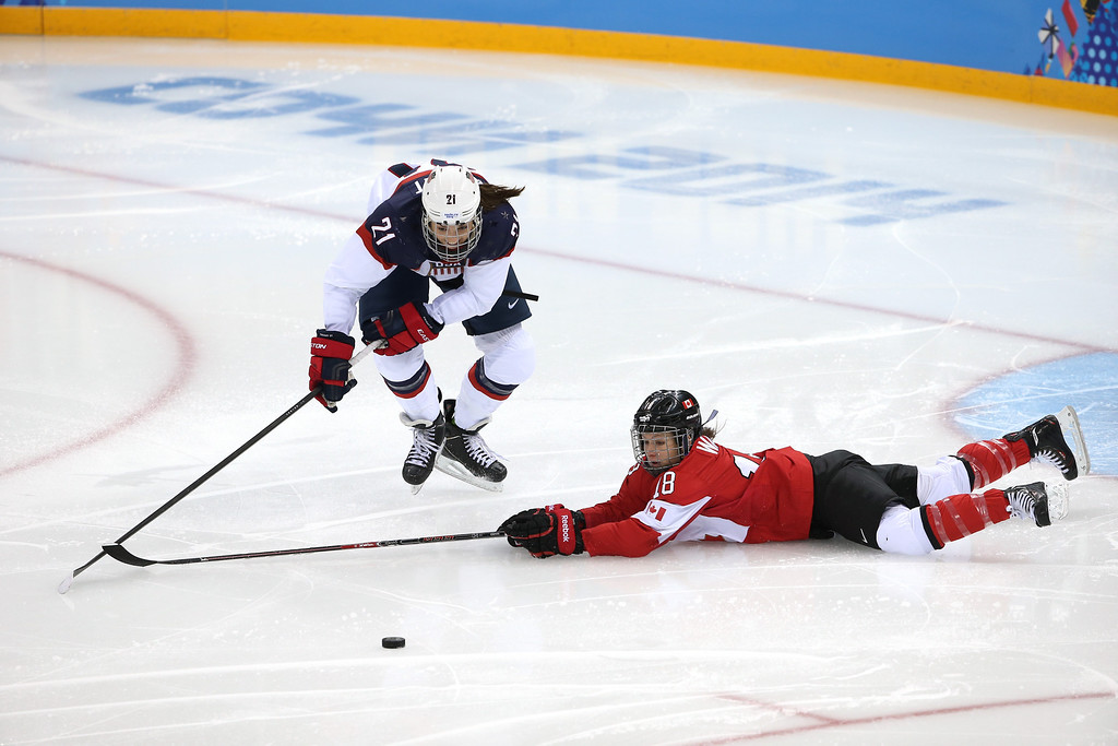 . Hilary Knight #21 of the United States and Catherine Ward #18 of Canada go for a loose puck in the second period during the Women\'s Ice Hockey Preliminary Round Group A game on day five of the Sochi 2014 Winter Olympics at Shayba Arena on February 12, 2014 in Sochi, Russia.  (Photo by Bruce Bennett/Getty Images)