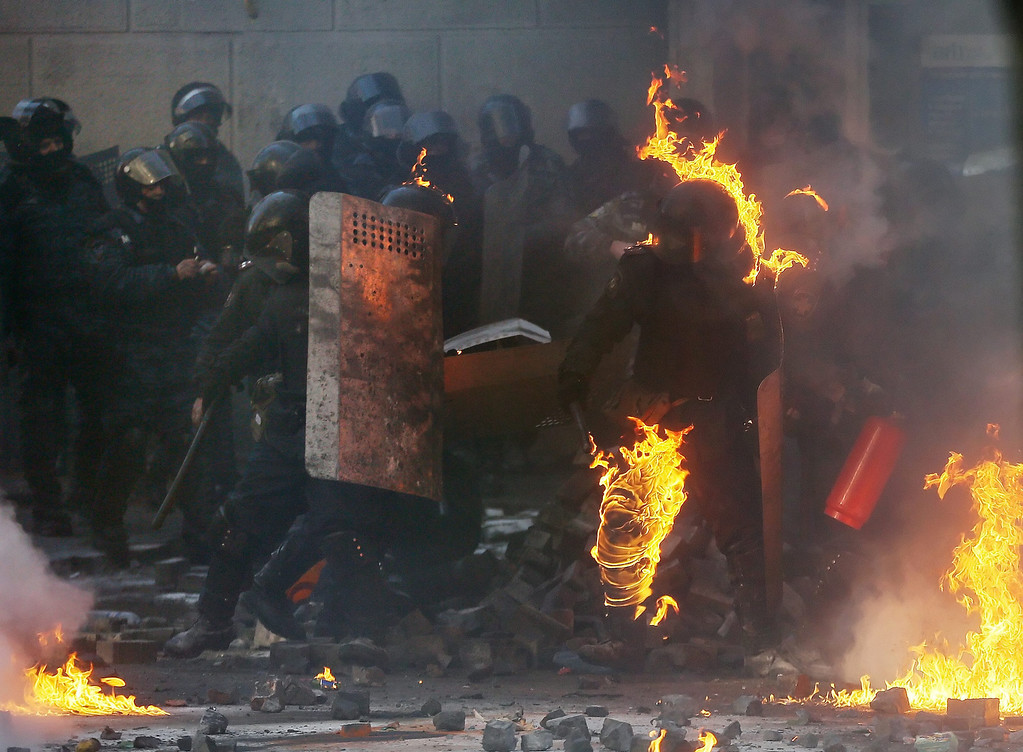 . A riot policeman is in flames during the continuing protest in downtown Kiev, Ukraine, 18 February 2014.  EPA/SERGEY DOLZHENKO