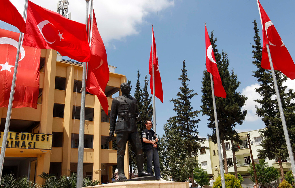 """. A police officer stands next to a statue of Mustafa Kemal Ataturk, the founder of modern Turkey, as he waits for the arrival of Turkey\'s President Abdullah Gul in the town of Reyhanli, in Hatay province near the Turkish-Syrian border May 16, 2013. Gul criticised the world\'s response to the Syria conflict on Thursday as limited to \""""rhetoric\"""", saying his country had received little help in coping with a huge influx of Syrian refugees. \""""The international community\'s contribution to Turkey\'s financial aid to these people who are in a difficult situation is only symbolic,\"""" Gul told reporters in Reyhanli where car bombs killed 51 people at the weekend. REUTERS/Umit Bektas"""