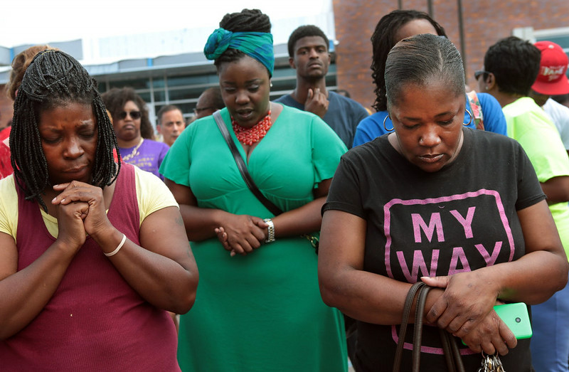 """. A prayer vigil was held in front of the Ferguson, Mo. police department on Sunday, Aug. 10, 2014, one day after a Ferguson officer shot and killed Michael Brown. From left are Martha Hightower, Leah Clyburn and Marie Wilson. \""""I\'m just tired of (the police) getting away with killing our youths,\"""" said Hightower. (AP Photo/St. Louis Post-Dispatch, Robert Cohen)"""