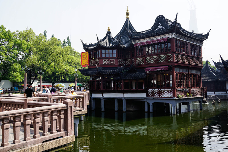 """Yu Garden is located at the northeast corner of the old city in south Shanghai. It was first built in 1559 (Ming Dynasty). The famous Yuyuan Market is near it.  Renowned traditional landscape garden in Jiangnan, it is also an historical site and tourist attraction. In 1982, it was listed as an important relic protection unit.  There are six main tourist sections in Yu Garden. Each section has its own special sights. After entering the garden, there is a big rockery with springs and small waterfalls.  It is considered the best rockery in Jiangnan district. The building """"Cui Xiu Tang"""" is the main sight in this section.  From the building """"Yu He Xie"""" to """"Wan Hua Lou"""", there are exquisite corridors, rivers, rockeries, courtyards. The stone hill – Jade Exquisite (Yu Ling Long in Chinese) is the treasure of the Yu Garden. It is considered the best of the famous three stones in Jiangnan district.  Facing the Jade Exquisite is the building """"Yu Hua Tang"""". Inside the building there is a traditional sanctum of the Ming Dynasty.  All of the desks and chairs are made of precious rosewood.  The Inner Garden is also called the East Garden.  It was first built in 1709 (during the Qing Dynasty). There are many rockeries, halls, pavilions, corridors, etc.  All of the buildings are arranged at random.  The main building in this garden is Qing Xue Tang. It features a Chinese traditional landscape garden.  Outside the garden there is a water lily pool.  Many brick carvings, stone carvings, mud sculptures, and wood sculptures are interspersed in the Yu Garden.  Among them, The Eight Immortals Going across the Sea, Guanghan Palace, etc.  Many famous artists in the Ming Dynasty wrote poems and painted here.  After hundreds of years there are now thousands of precious paintings, furniture, porcelains, etc.  The garden was built by Pan during the Ming Dynasty.  It was changed and rebuilt for hundreds of years by different descendents of the original builder.  The garden is a maze of caves, g"""