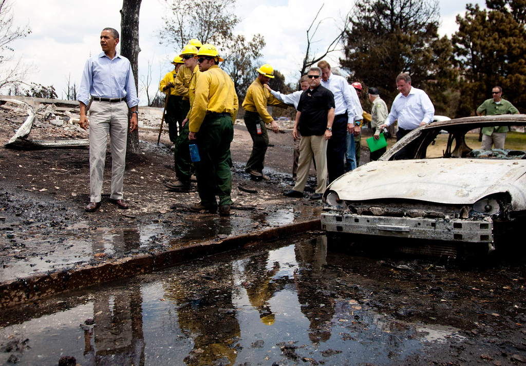 . President Barack Obama talks to firefighters as he tours the Mountain Shadow neighborhood devastated by raging wildfires, Friday, June 29, 2012, in, Colorado Springs, Colo. (AP Photo/Carolyn Kaster)