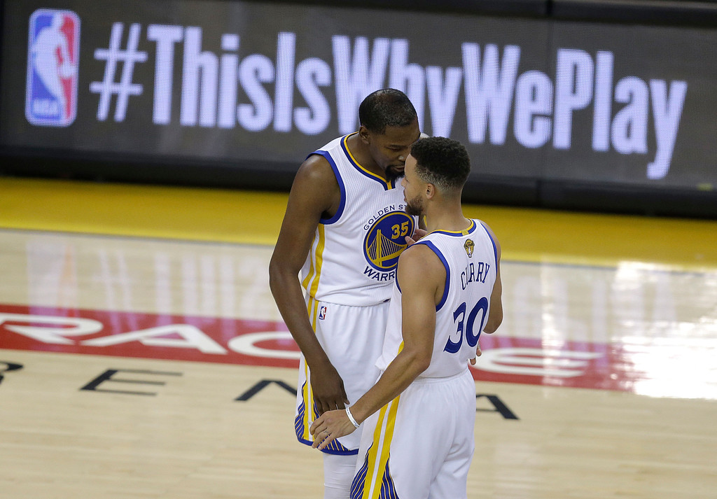 . Golden State Warriors forward Kevin Durant (35) talks with guard Stephen Curry (30) during the first half of Game 2 of basketball\'s NBA Finals against the Cleveland Cavaliers in Oakland, Calif., Sunday, June 4, 2017. (AP Photo/Ben Margot)